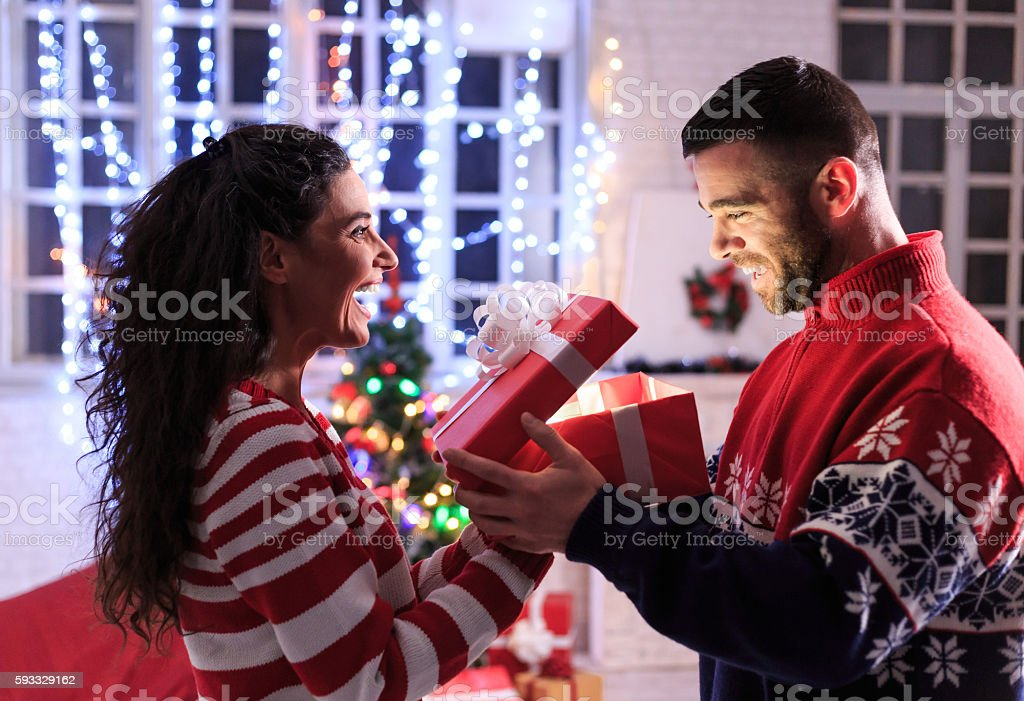 Young woman giving christmas present to her man stock photo