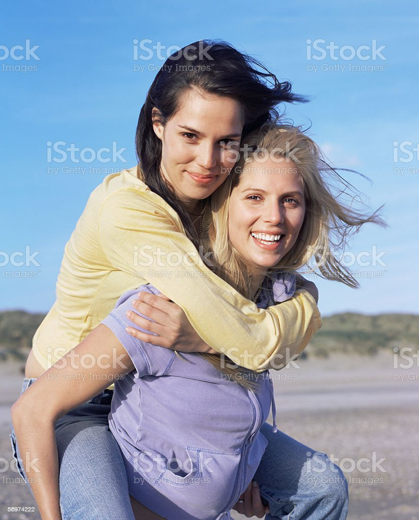 Young woman giving friend a piggyback royalty-free stock photo