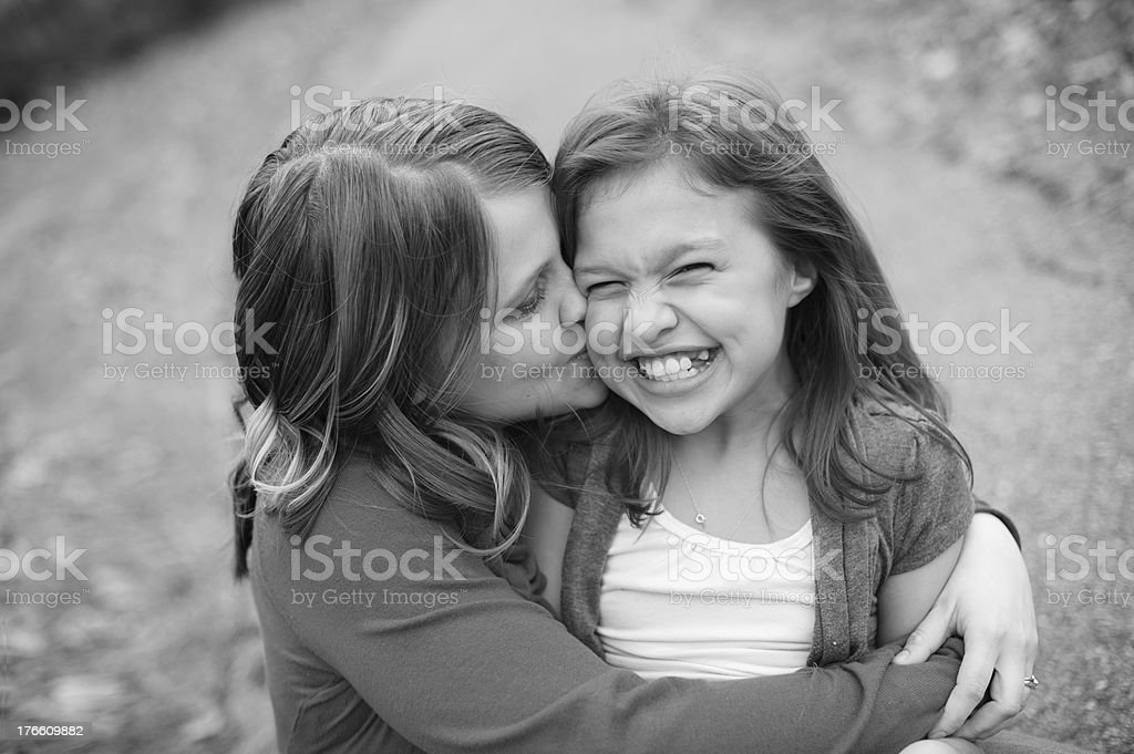 Young Woman Giving Laughing Little Sister Kiss on Cheek royalty-free stock photo