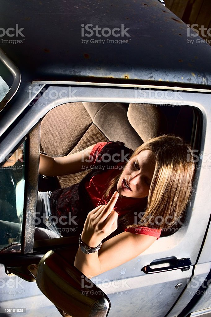 Young Woman Giving Middle Finger Gesture While Driving royalty-free stock photo