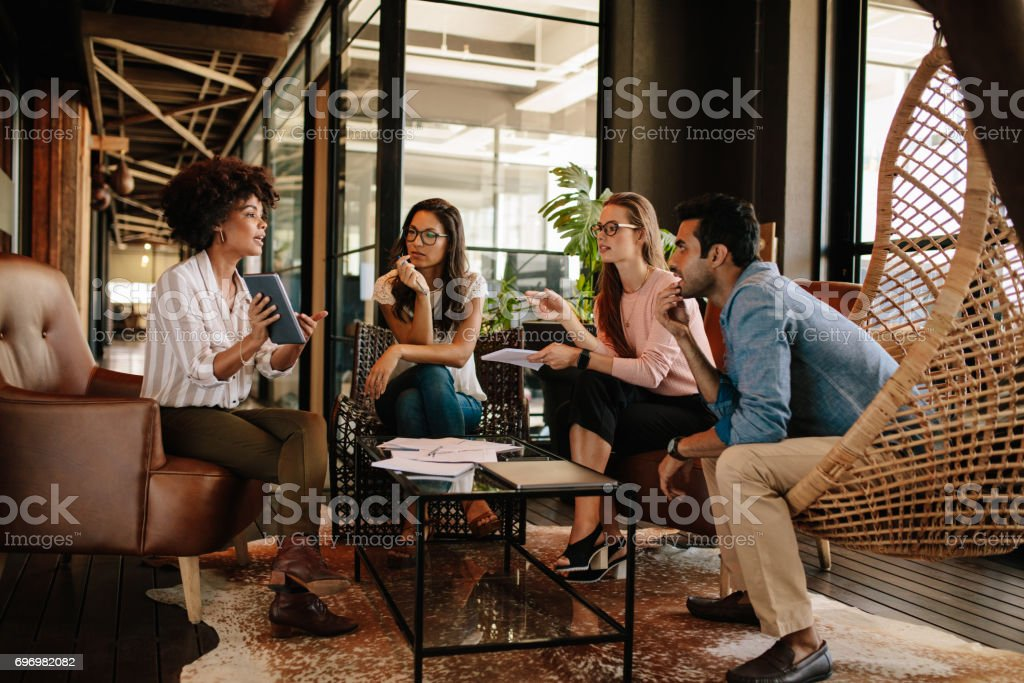 Young woman giving presentation to colleagues at office stock photo
