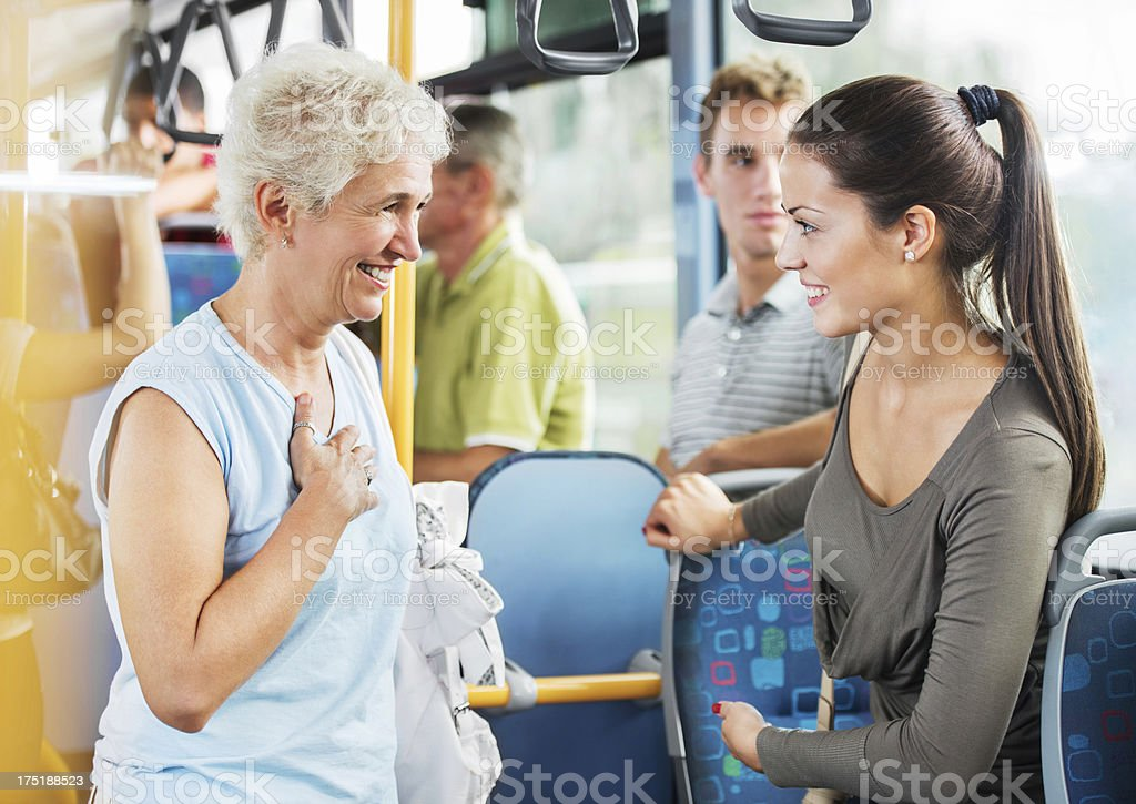 Young woman giving up her seat to elderly woman. stock photo