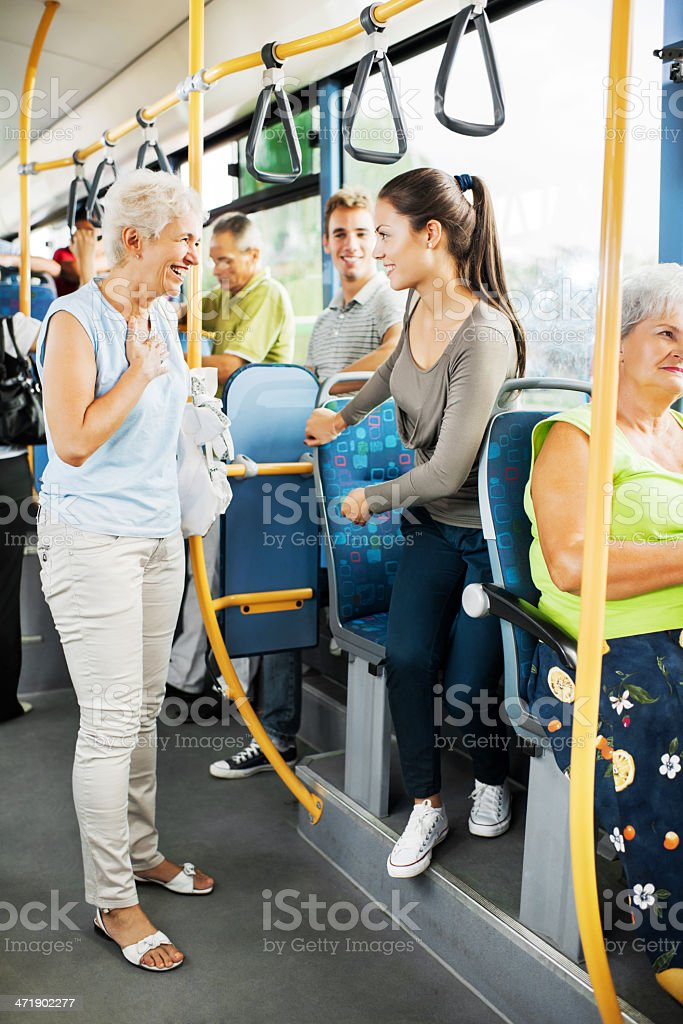 Young woman giving up her seat to elderly woman. royalty-free stock photo