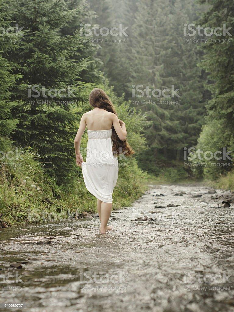 Jeune femme va pieds nus sur la rivière de montagne photo libre de droits