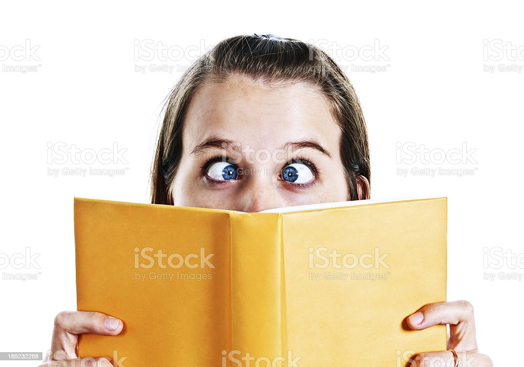 Young woman goes cross eyed over yellow book stock photo