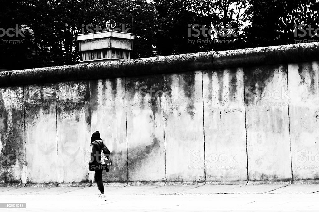 Young woman goes to the Berlin Wall along stock photo