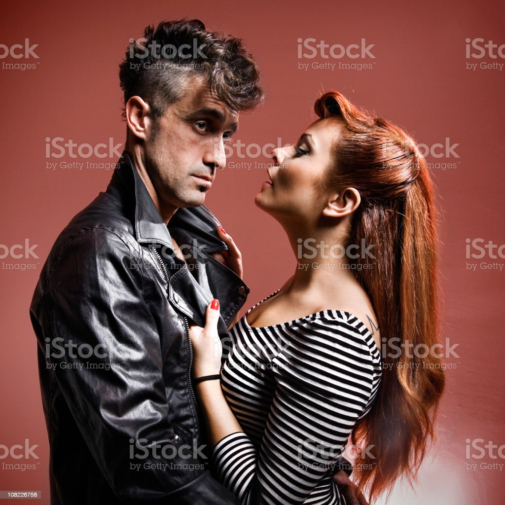Young Woman Grabbing Jacket of Man Holding Her stock photo