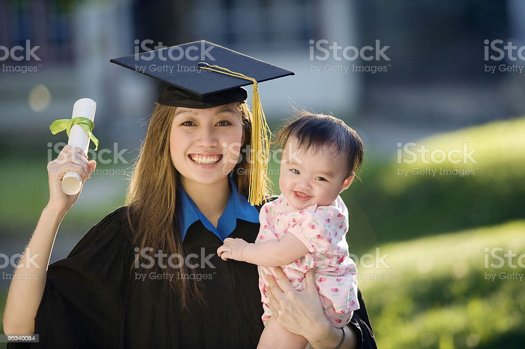 Young woman graduate holding baby royalty-free stock photo