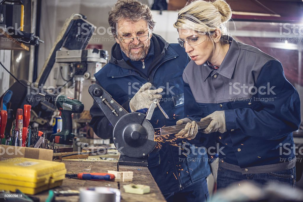 Young Woman Grinding Metal in Mechanical Workshop stock photo