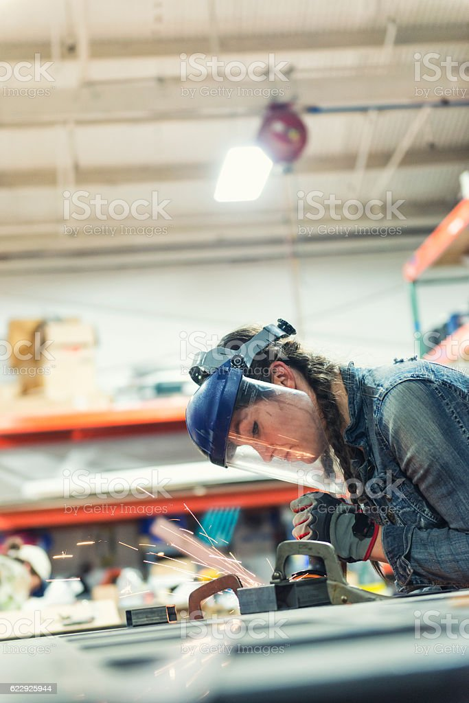 Young woman grinding metal stock photo