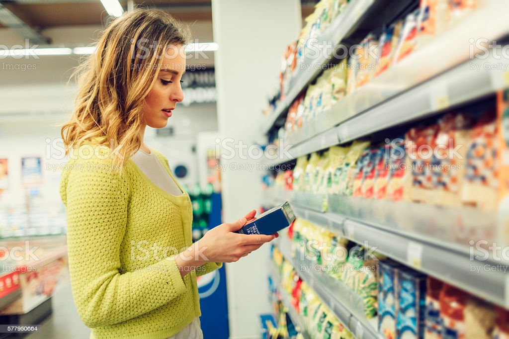 Young Woman Groceries Shopping In Local Supermarket. stock photo