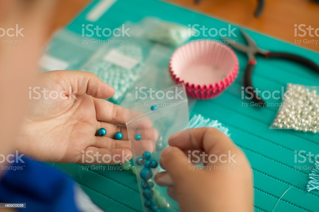 Young woman handcrafting with colourful beads stock photo