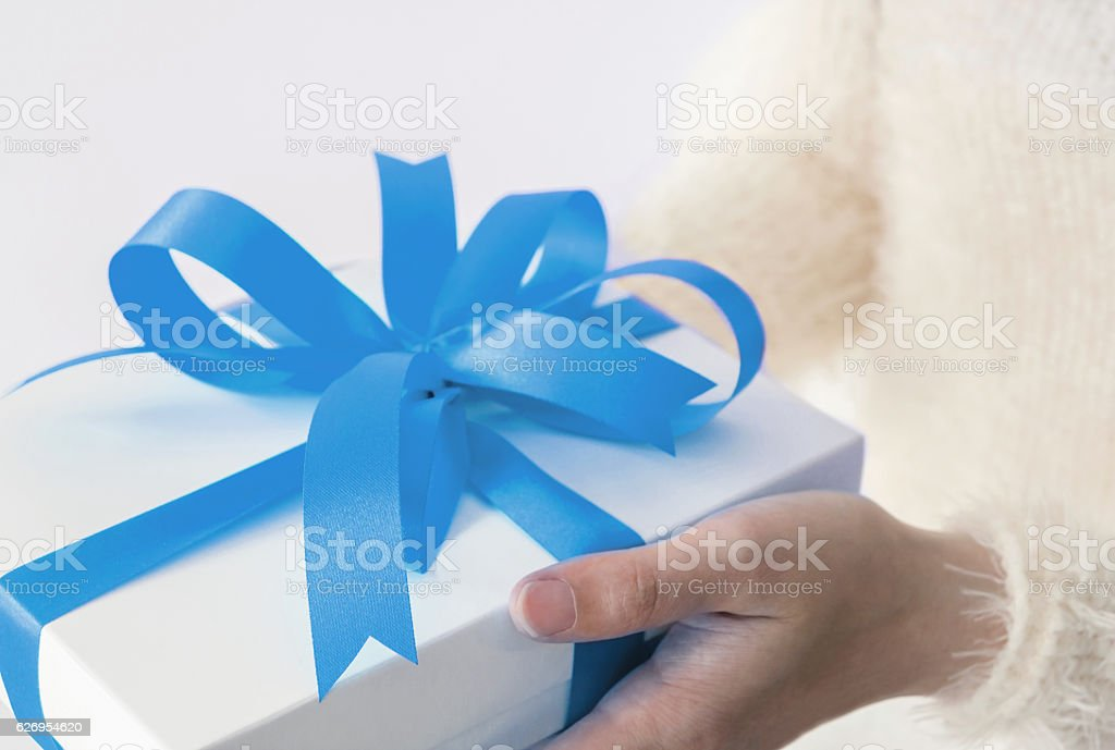 Young woman hands holding gift box stock photo