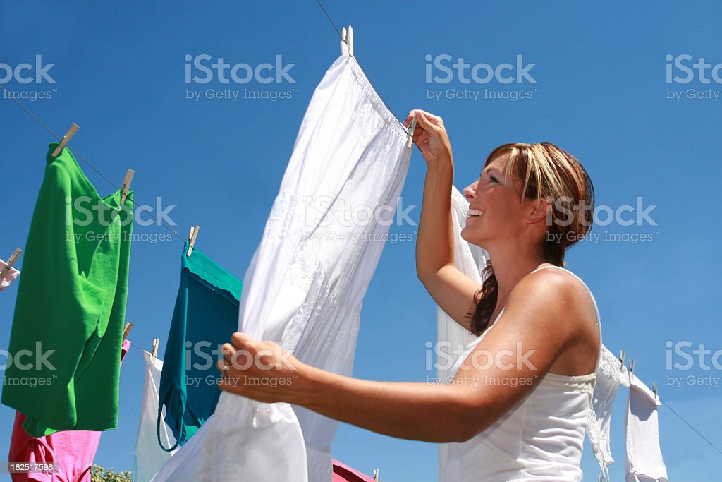 A young woman hanging her laundry to dry outside royalty-free stock photo