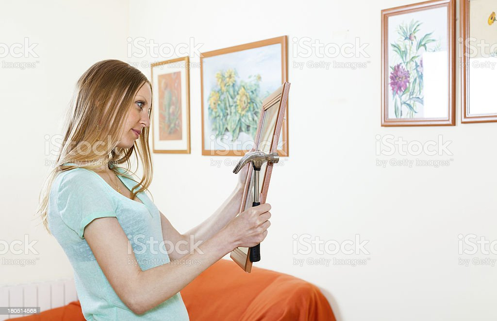 young woman hanging pictures  at home royalty-free stock photo