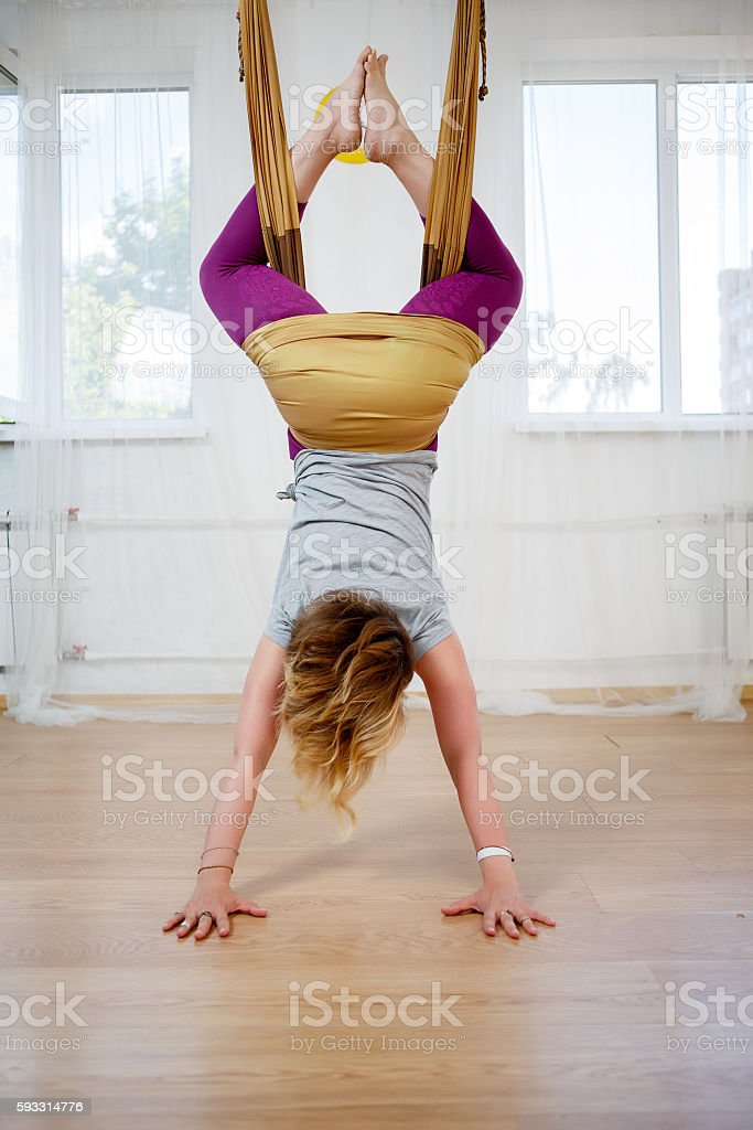 Young woman hanging upside down and practicing fly yoga stock photo