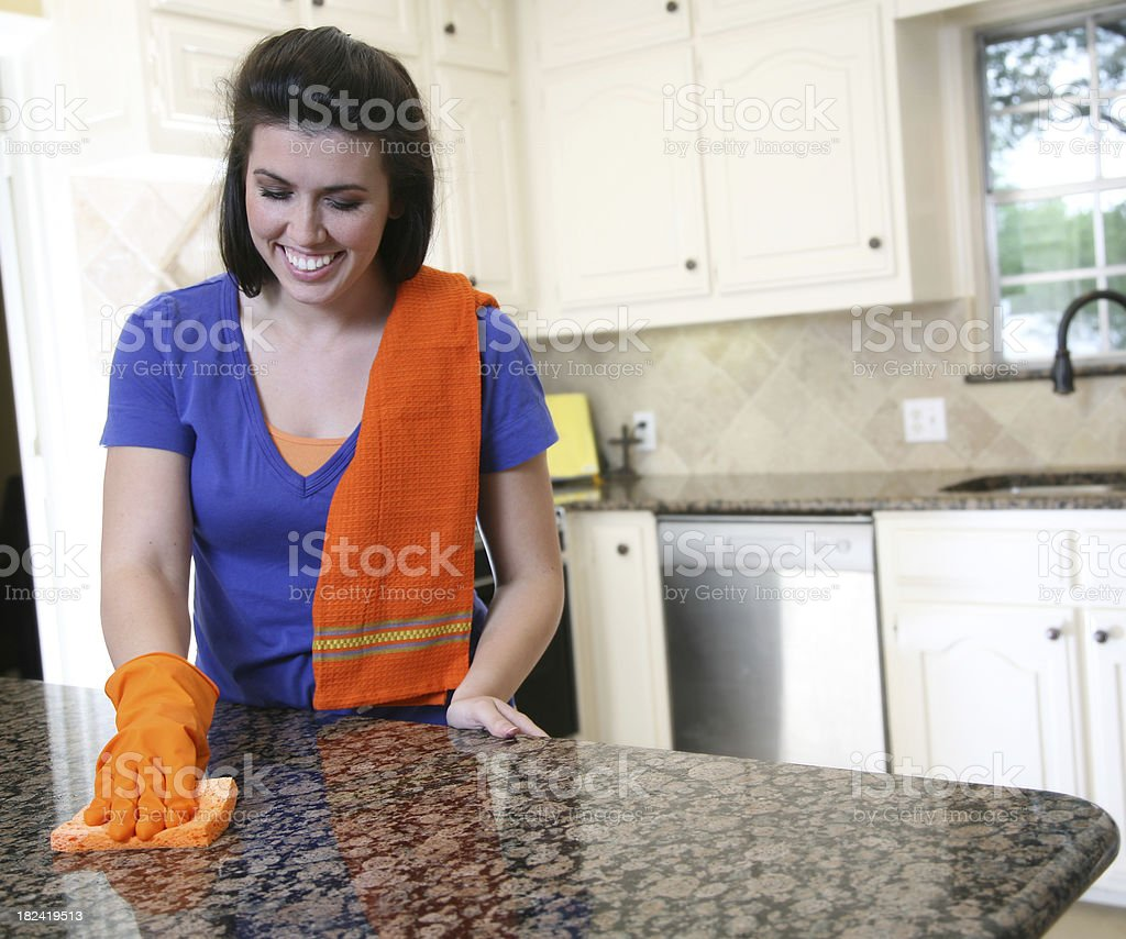 Young Woman Happily Cleaning Her Kitchen Counter With Orange Sponge royalty-free stock photo