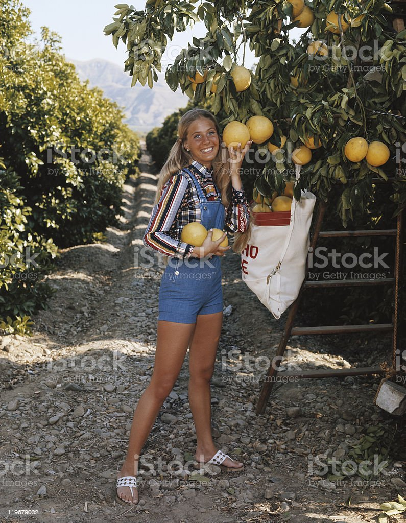 Young woman harvesting pummelo, smiling, portrait royalty-free stock photo