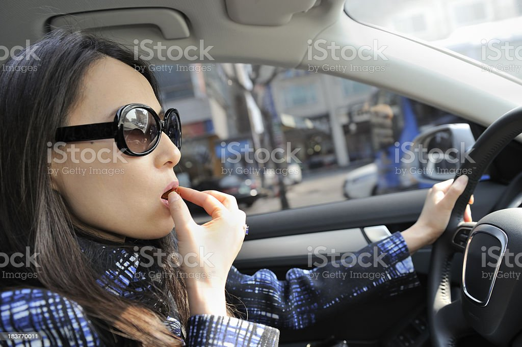 Young woman having a bite while driving royalty-free stock photo