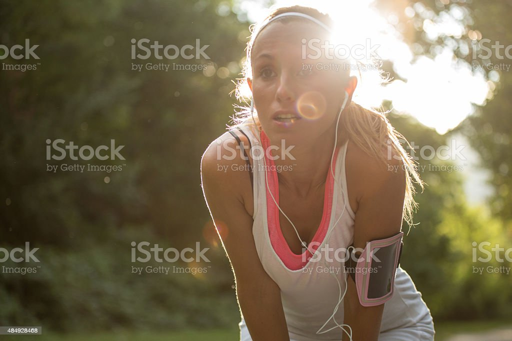 Young woman having a break after running outdoors stock photo