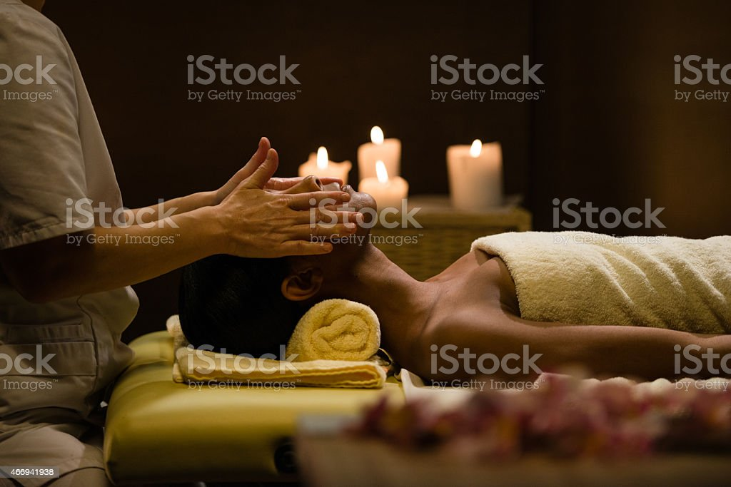Young Woman Having a Head Massage in a Relaxing Atmosphere stock photo