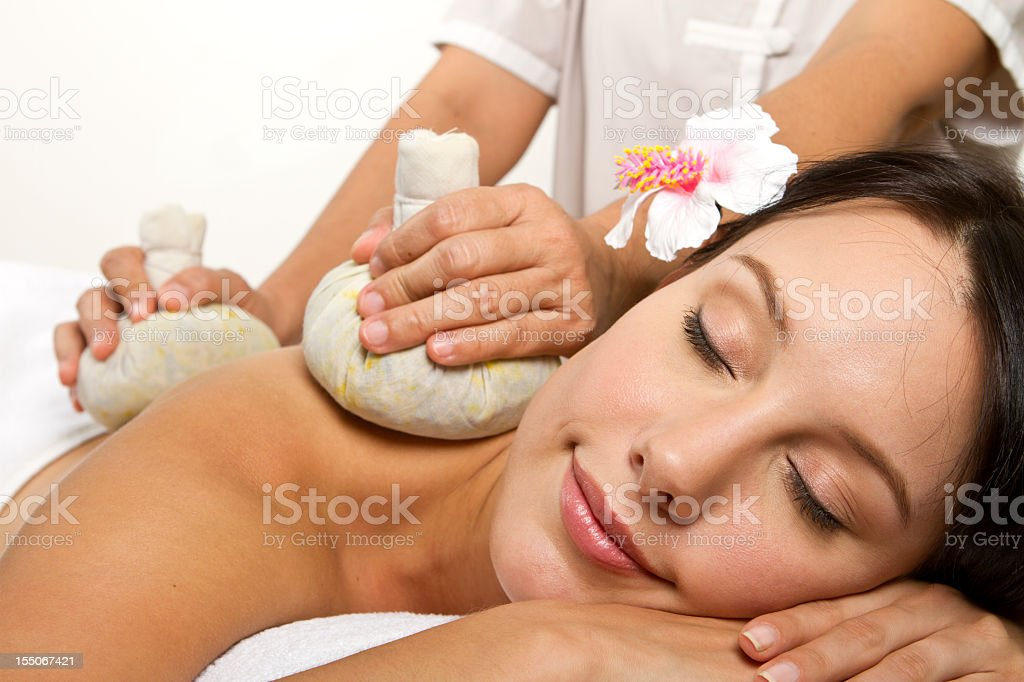 Young woman having a herbal compress massage treatment royalty-free stock photo