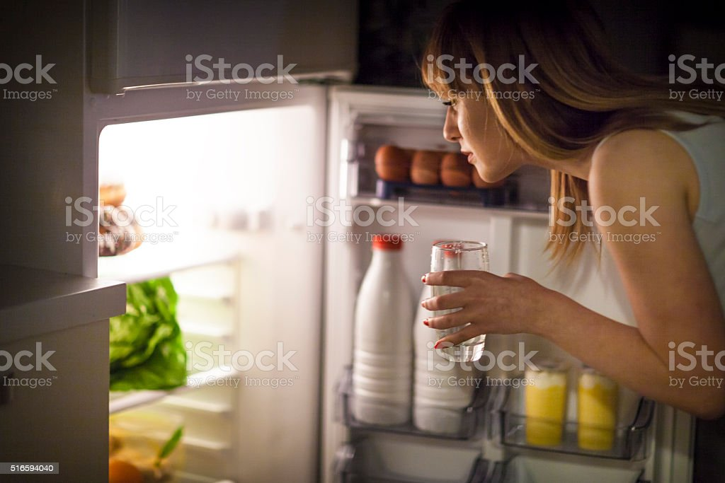 Young woman having a midnight snack stock photo
