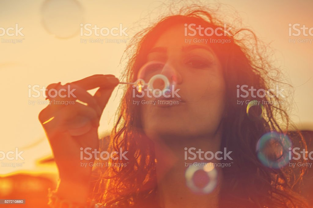 Young woman having blowing bubbles stock photo