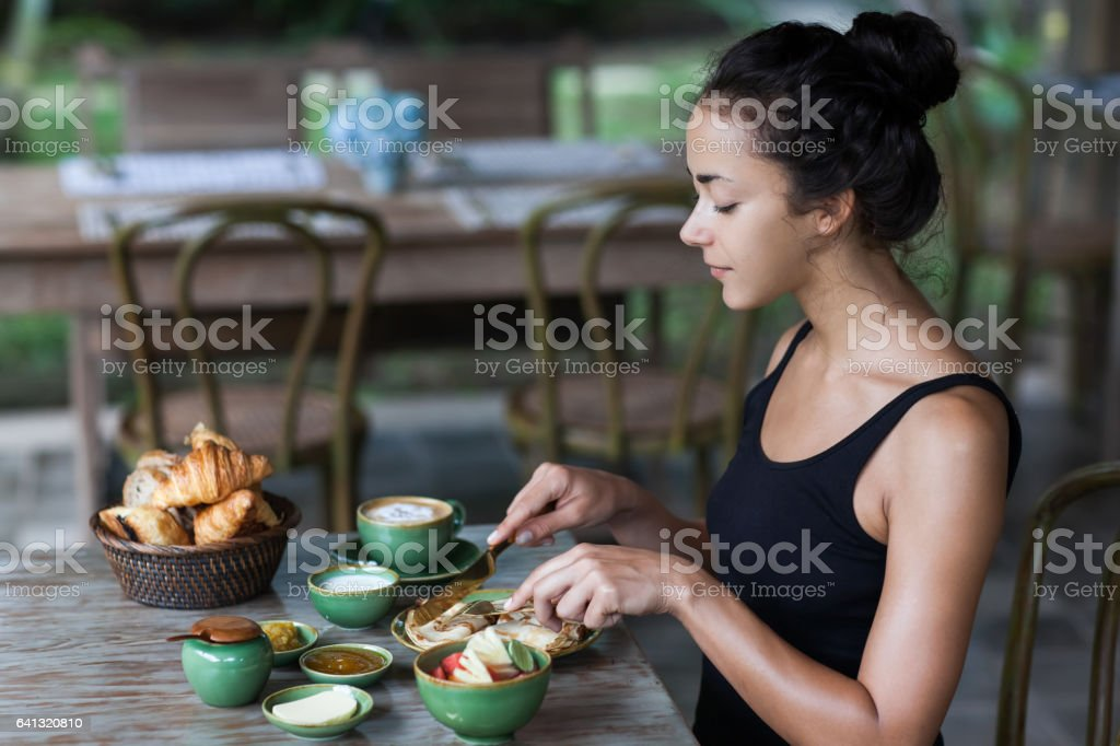 Young woman having breakfast and cut pankaces with golden fork and knife stock photo