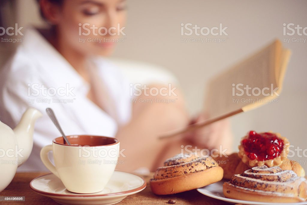 young woman having breakfast and reading a book stock photo