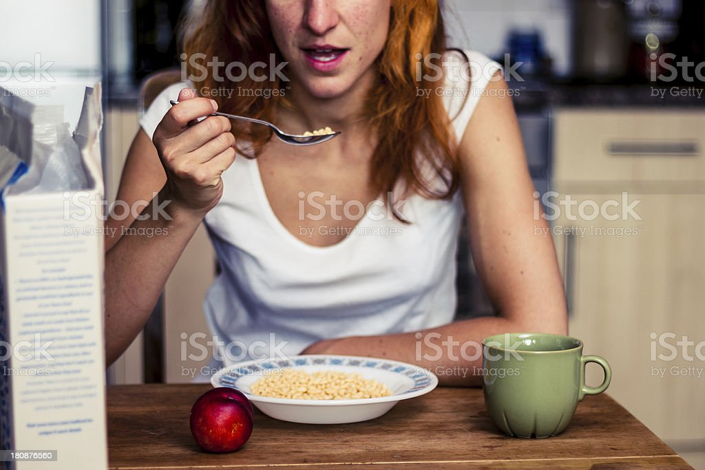 Young woman having cereal and fruit for breakfast royalty-free stock photo