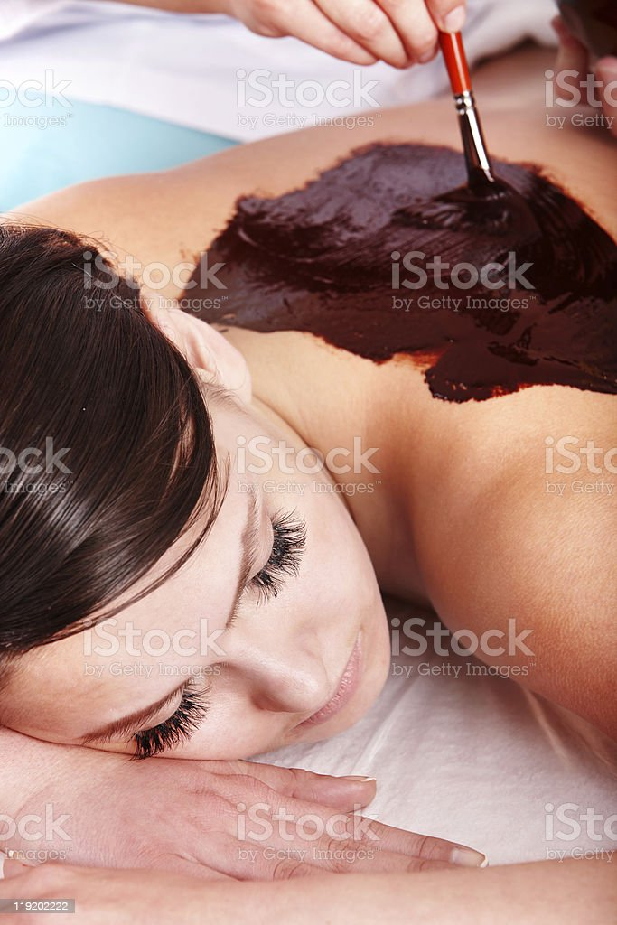 Young woman having chocolate body mask. royalty-free stock photo