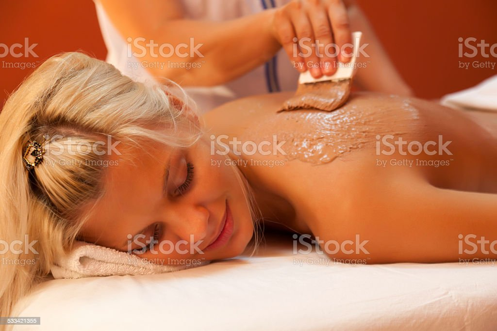 Young woman having chocolate body mask. stock photo