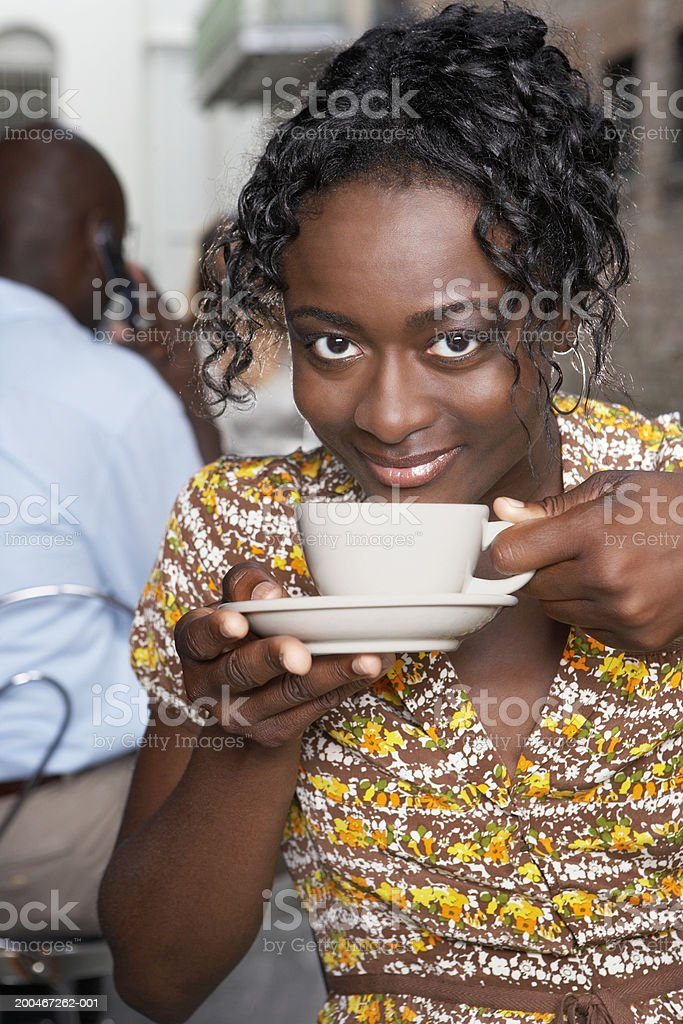 Young woman having coffee in outdoor cafe, smiling, portrait royalty-free stock photo