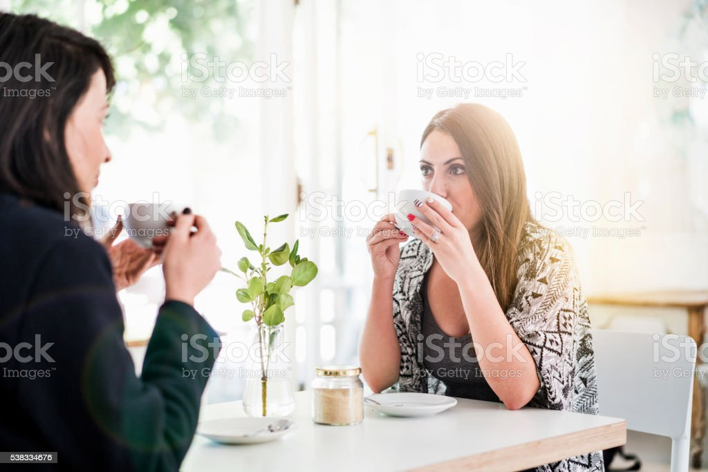 Young woman having coffee with friend in cafe stock photo