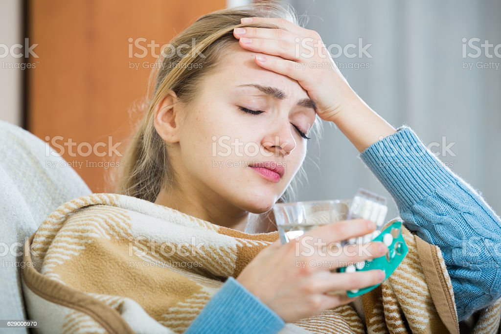Young woman having cold under plaid at home stock photo