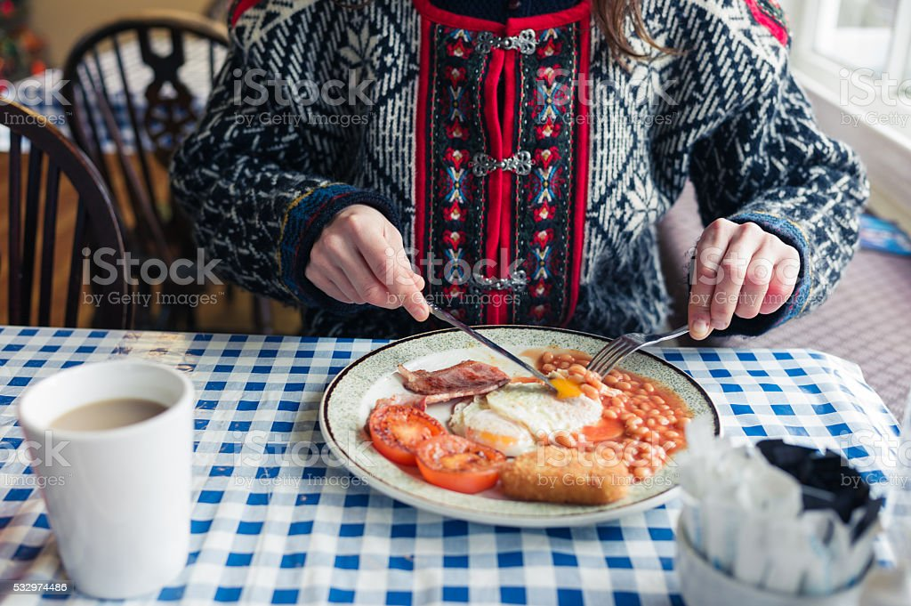 Young woman having english breakfast stock photo