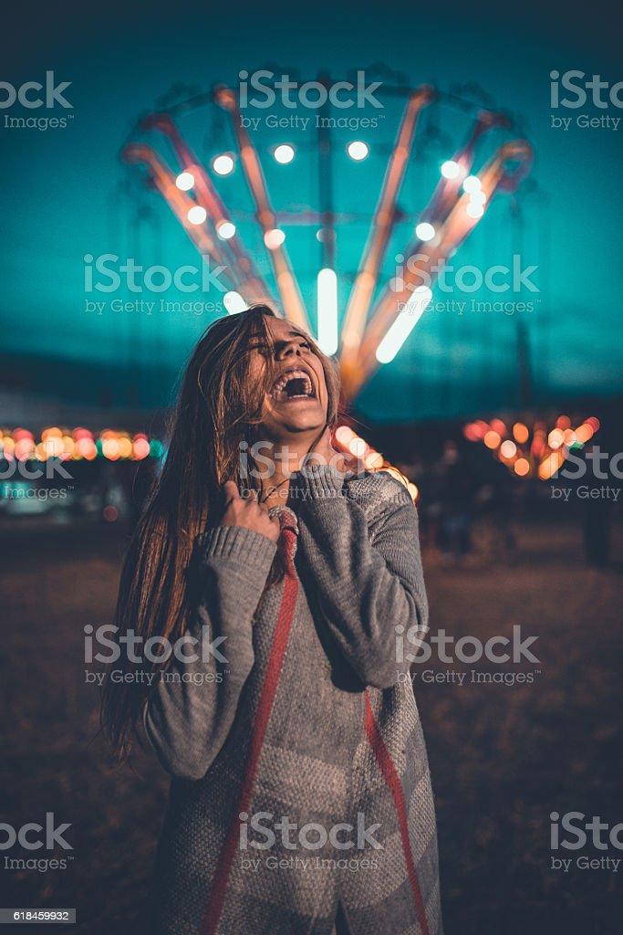 Young Woman Having Fun in Amusement Park Fair at Night stock photo