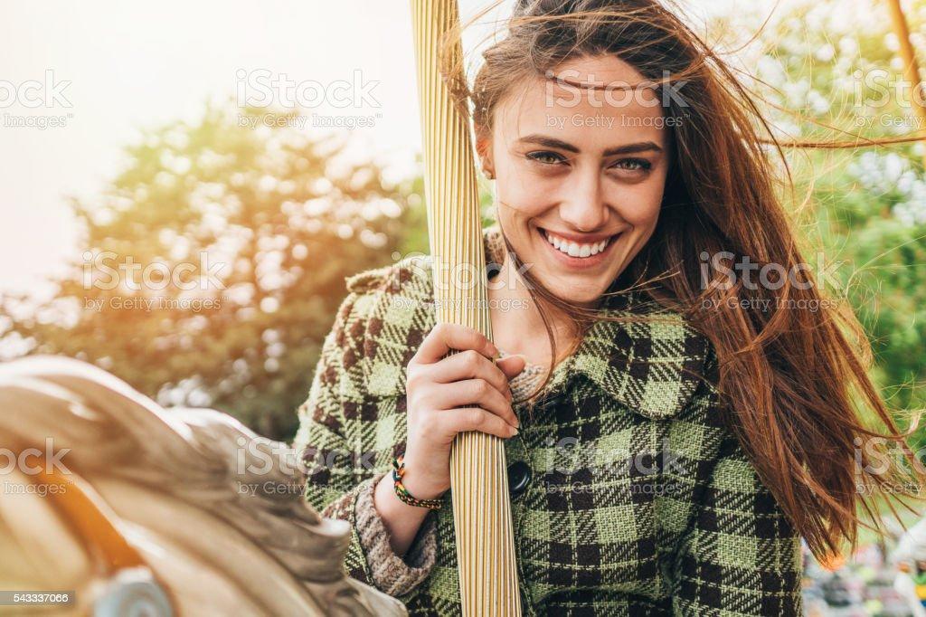 Young woman having fun on a carousel stock photo