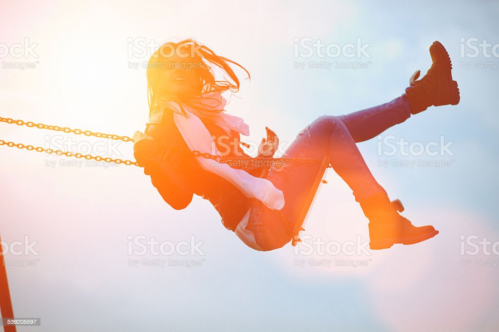 Young woman having fun swinging in sunlight stock photo