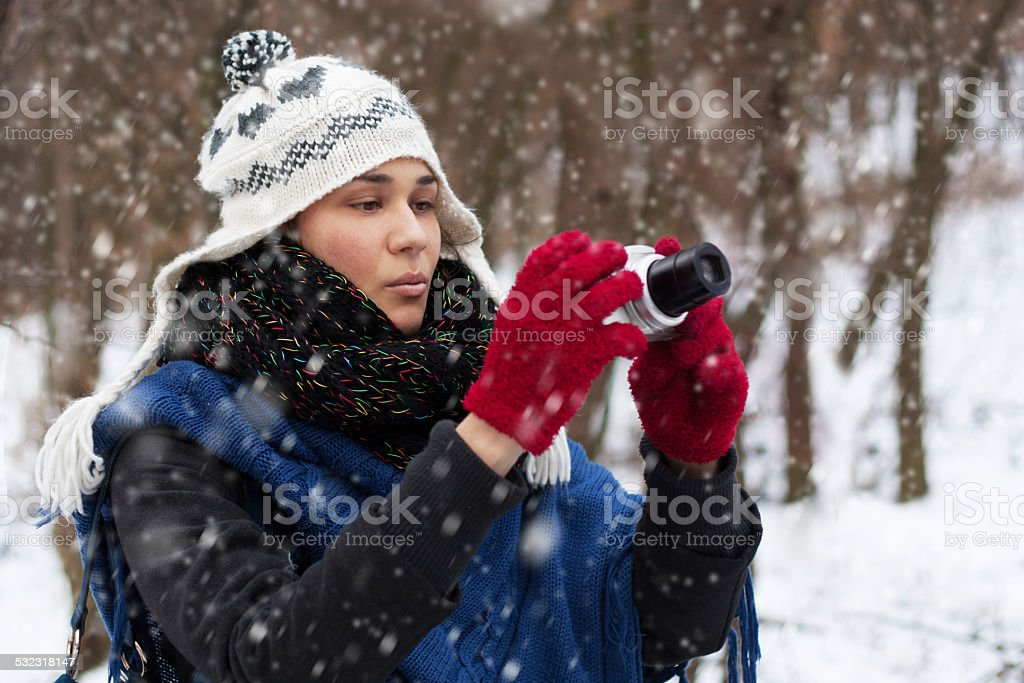 Young Woman having fun with camera in Snowy Weather stock photo