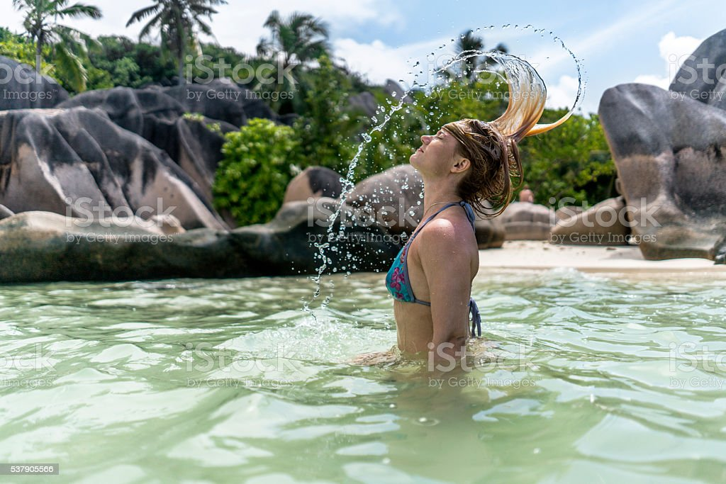 Young woman having fun with her hair in the sea. stock photo