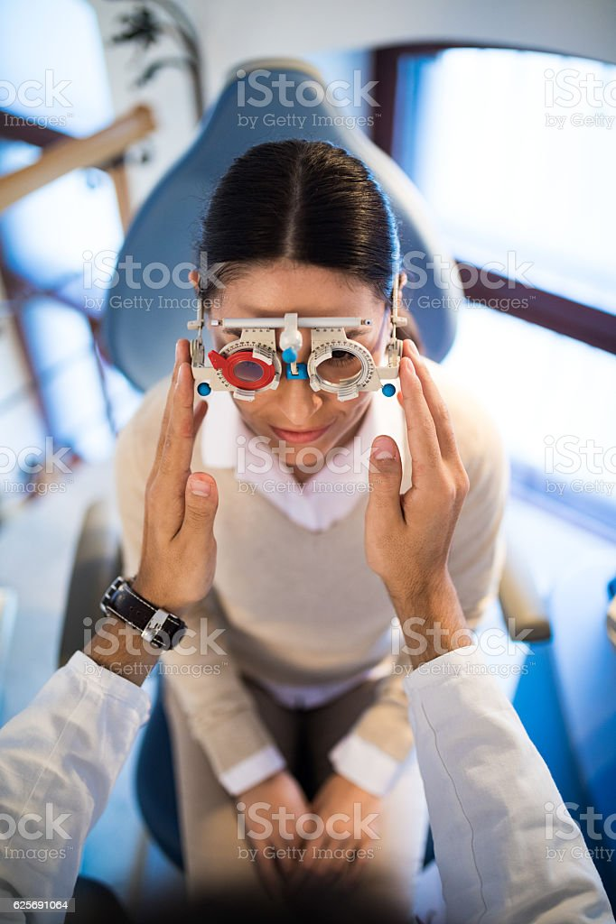 Young woman having her eyes examined by optometrist. stock photo