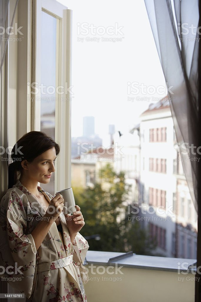 Young woman having morning coffee at open window stock photo