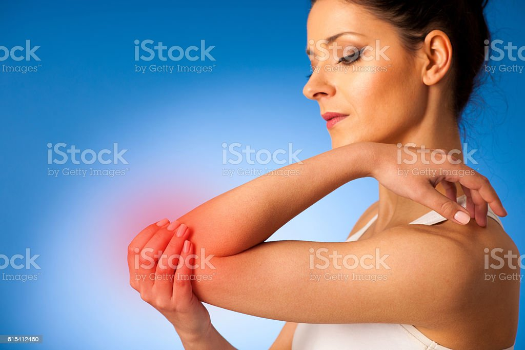 young woman having pain in injured elbow stock photo