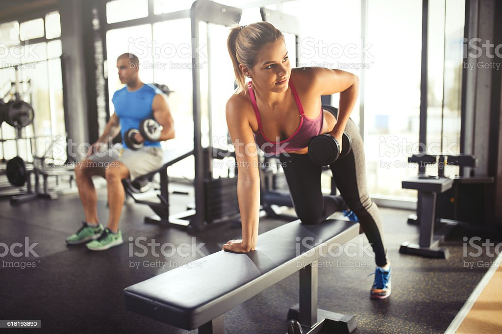 Young woman having weight training with dumbbells at gym . stock photo