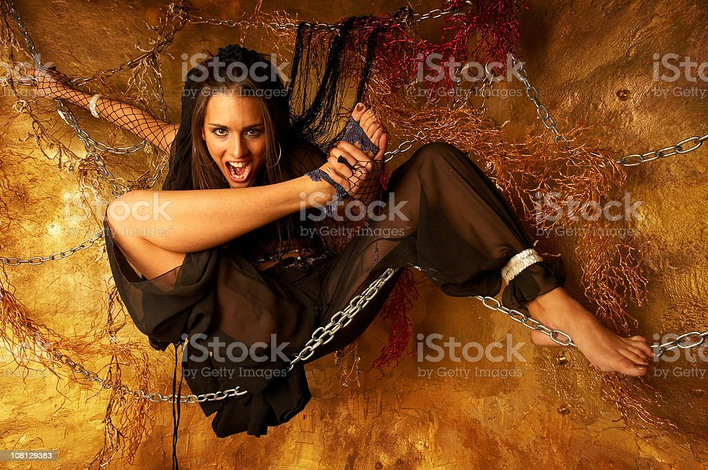 Young Woman Held In Chains on Golden Background royalty-free stock photo