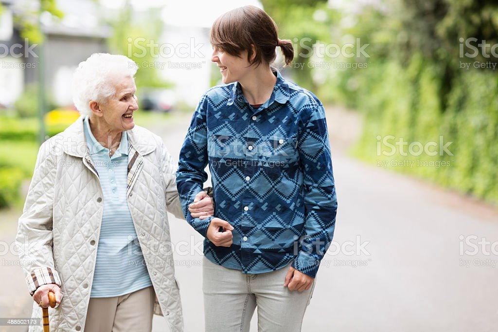 Young woman helping elderly woman walk down street stock photo