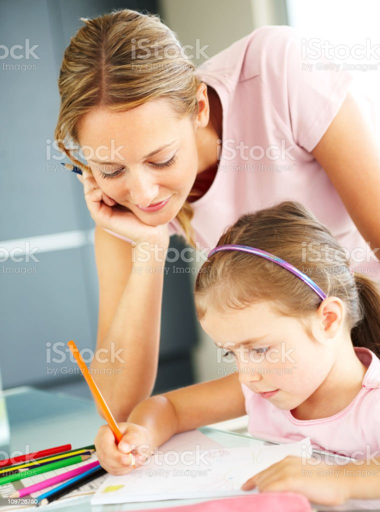 Young woman helping her daughter in drawing royalty-free stock photo