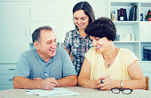 Young woman helping her mature  parents to do paperwork